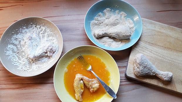 Die Hühnerteile kommen in eine klassische Panier aus Mehl, Ei und Semmelbrösel.