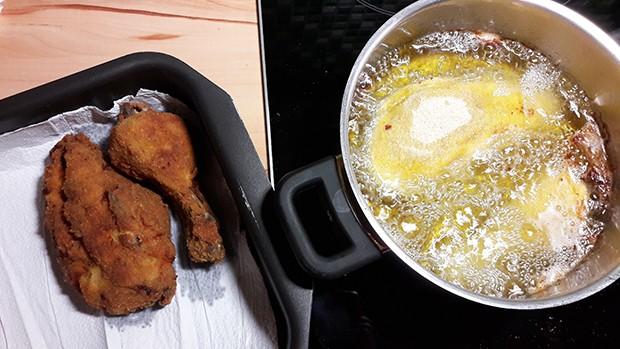 Die panierten Hendlteile werden in reichlich Öl frittiert.